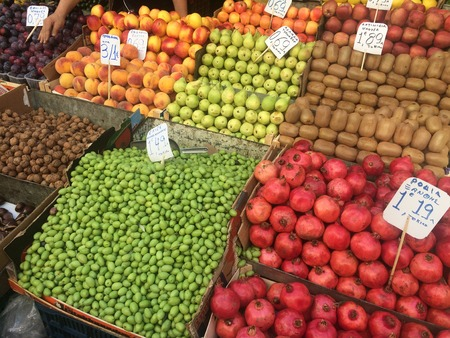 A lot of fruits in boxes in the market with price tags.