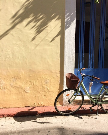 An old green bicycle with a wicker basket on the handlebar stands near the colored wall. The blue door and the yellow wall. Beautiful shadow from a tree on a yellow wall. Summer. Summer wallpaper on the phone. 版權商用圖片