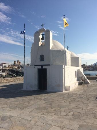White othodox church, Greece, with a flags. White chapel on a shore. 版權商用圖片