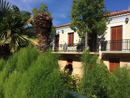 The balconies of the house are hidden in the trees. Little orange villa in a hidden garden 版權商用圖片 - 98782743