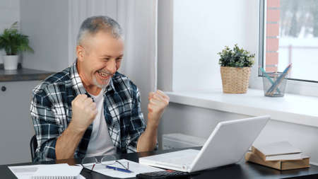 A happy elderly man enjoys the good news while looking at his laptop at home.