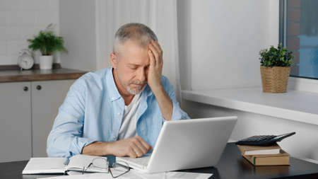 A tired old man, leaning on his arm sleeps at a desk in front of a laptop.