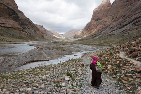A pilgrims walks in barren Lha-chu valley on the path around Mt. Kailash, TIbet, China - one of the most important pilgrimage routes for Buddhists and Hindus.