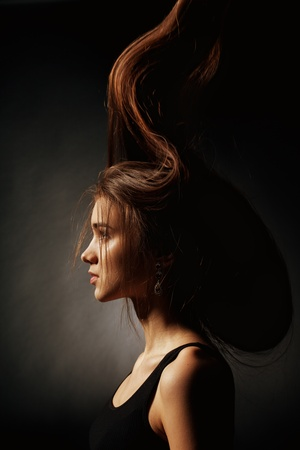 Portrait of a young girl with very long hair on a black background