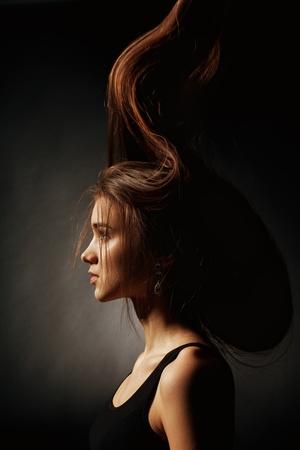 Portret van een jong meisje met lange haren op een zwarte achtergrond Stockfoto