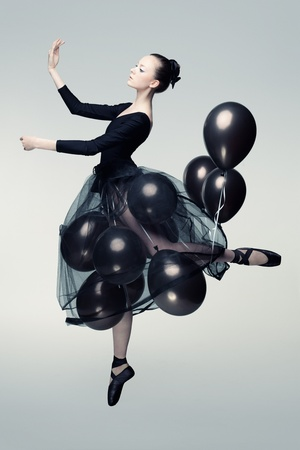 Studio photo of a young ballet dancer flying away on balloons. photo