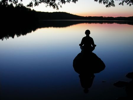 woman meditating on rock photo