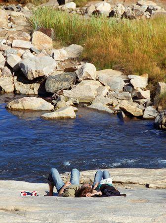 lovers on a rock Фото со стока
