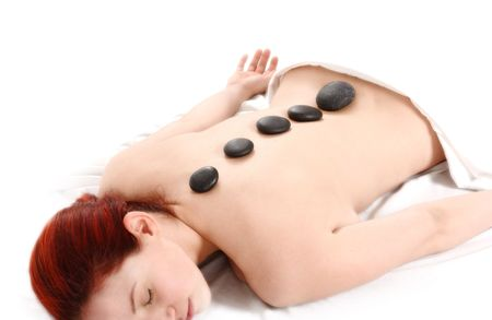 woman getting a hot stone massage on white background photo