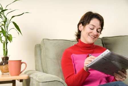 woman smiling and searching in the newspaper Stock Photo - 621660