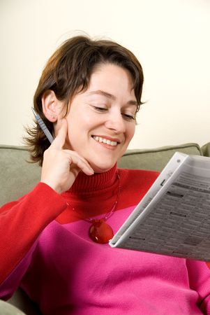 cute woman reading the newspaper on couch photo