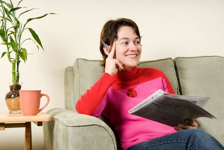 cute woman on couch looking at newspaper photo