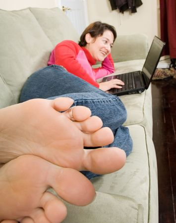 woman on couch: casual laptop surfing with feet in forground