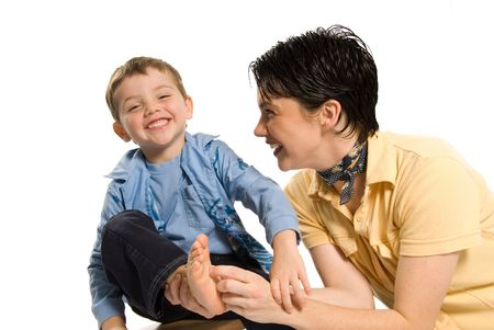 mom tickling sons feet on white isolated background photo