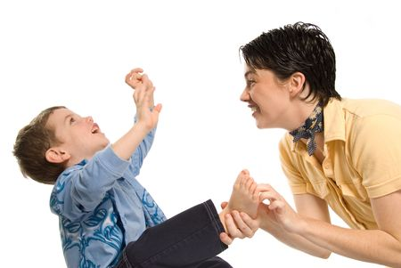 family tickle: son being tickled by mom on white background Stock Photo