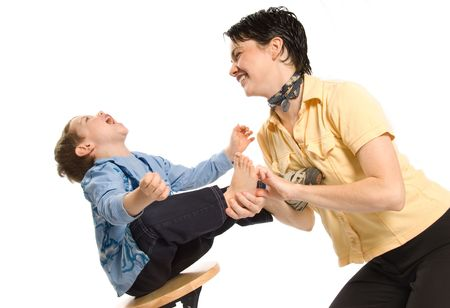family tickle: mom tickling sons feet and laughing hard Stock Photo