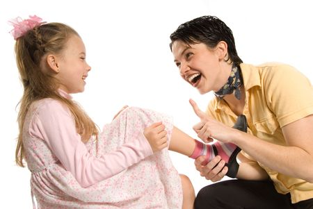 family tickle: mom and daughter having a blast on white background Stock Photo