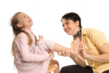 family tickle: mom tickling daughter on white background laughing Stock Photo