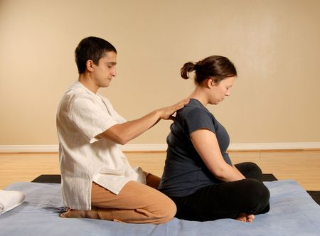 therapist giving a thai massage to pregnant woman