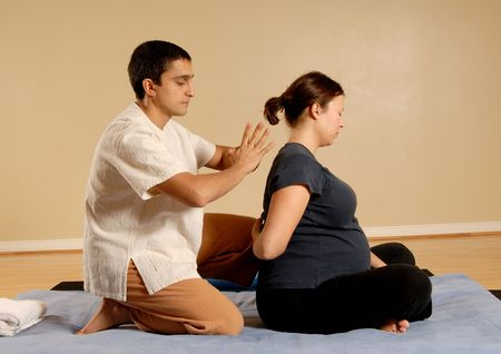 therapist giving thai massage to female client