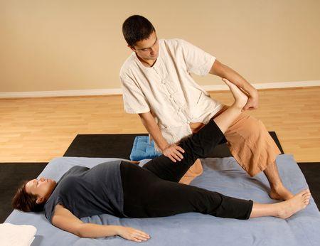 man therapist stretching woman leg in massage