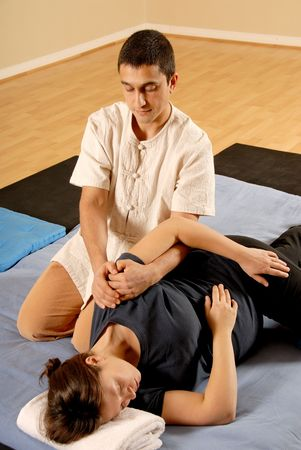 hand on shoulder: man therapist stretching female client in massage Stock Photo