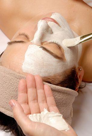 얼굴 표정: woman getting a facial with cream and a brush