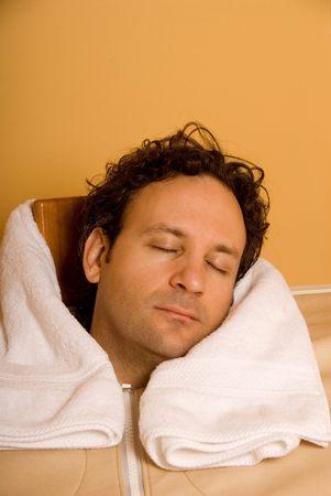 man sleeping in personal sauna at spa