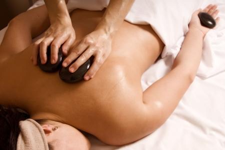 sports massage: Terapeuta da un masaje con piedras calientes al cliente