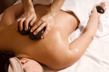 Therapist giving a hot stone massage to client photo