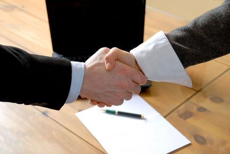 man and woman shaking hands in front of laptop