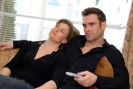sits: man watching TV whicle woman sits back bored Stock Photo