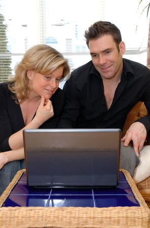 happy couple looking at their laptop in the living roon