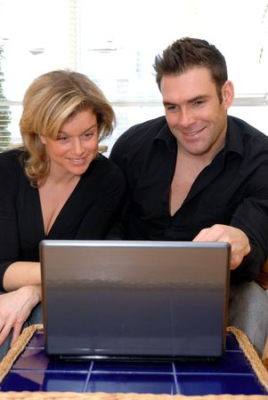 lovers working from home on their silver laptop photo