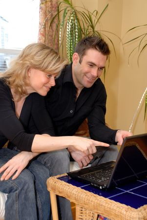 cute couple looking at emails on the couch on a wireless photo