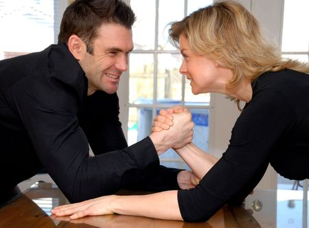 strong: angry couple fighting with some arm wrestling