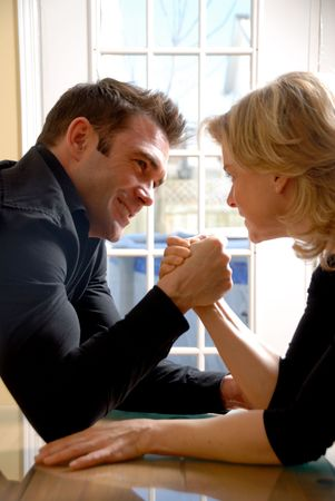 angry couple battling it off with some arm wrestling photo