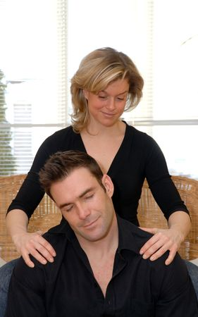 to rub: woman giving a shoulder rub to her man