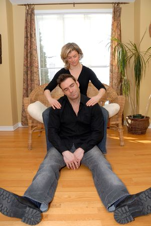 couple in the living room with woman giving a massage Фото со стока