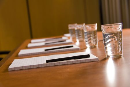 empty board room with water glasses and paper