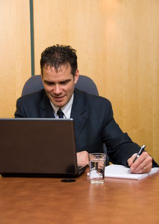 Businessman in a board room with his grey laptop Stock Photo - 820222