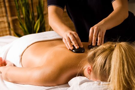 therapist giving a hot stone massage to woman