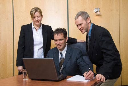 3 business people around a laptop in a meeting