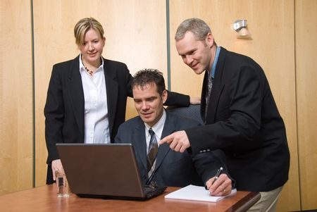 3 business people around a laptop in a meeting pointing