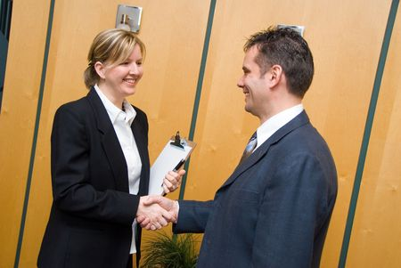 man and woman greeting each other in a reception area