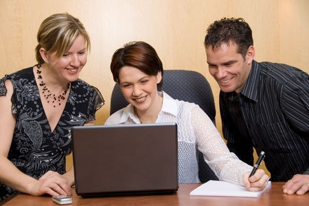 happy colleagues in an office with a laptop