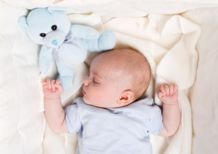 cute baby boy dreaming in his bed photo