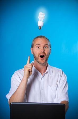 man wih a beard with a light bulb on the laptop photo