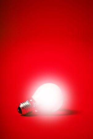 incandescent: incandescent light bulb on a red background
