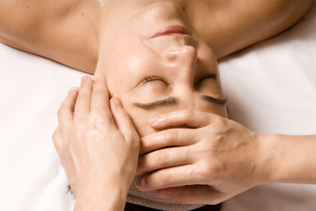 woman relaxing with a nice facial massage photo
